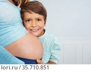 Happy son hug mom's pregnant belly close photo. Стоковое фото, фотограф Сергей Новиков / Фотобанк Лори