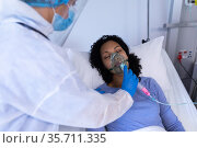 Caucasian doctor in ppe suit checking on female patient in hospital bed with oxygen ventilator. Стоковое фото, агентство Wavebreak Media / Фотобанк Лори