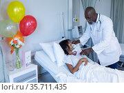 African american male doctor putting oxygen mask ventilator on sick mixed race girl in hospital bed. Стоковое фото, агентство Wavebreak Media / Фотобанк Лори