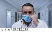 Portrait of smiling caucasian male doctor putting on face mask in hospital corridor. Стоковое видео, агентство Wavebreak Media / Фотобанк Лори