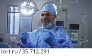 Portrait of mixed race male surgeon wearing lowered face mask smiling in operating theatre. Стоковое видео, агентство Wavebreak Media / Фотобанк Лори