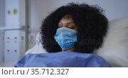Portrait of african american female patient wearing face mask lying on hospital bed. Стоковое видео, агентство Wavebreak Media / Фотобанк Лори