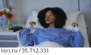 Mixed race woman lying in hospital bed fluffing her pillow. Стоковое видео, агентство Wavebreak Media / Фотобанк Лори