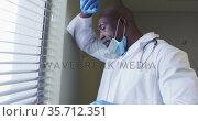Portrait of african american male doctor wearing face mask talking using smartphone. Стоковое видео, агентство Wavebreak Media / Фотобанк Лори