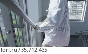 Tired african american male doctor walking down stairs in hospital. Стоковое видео, агентство Wavebreak Media / Фотобанк Лори