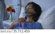 Portrait of african american female patient lying on hospital bed wearing oxygen mask ventilator. Стоковое видео, агентство Wavebreak Media / Фотобанк Лори