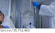 Diverse male doctor preparing drip bag for female patient in hospital room. Стоковое видео, агентство Wavebreak Media / Фотобанк Лори