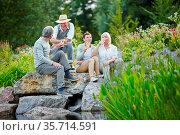 Zufriedene Senioren sitzen mit einem Glas Weißwein im Sommer im Garten. Стоковое фото, фотограф Zoonar.com/Robert Kneschke / age Fotostock / Фотобанк Лори