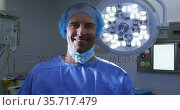 Portrait of smiling male caucasian surgeon with face mask and scrubs in hospital. Стоковое видео, агентство Wavebreak Media / Фотобанк Лори