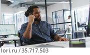 Mixed race businessman sitting at desk looking at computer screen, using smart phone and smiling. Стоковое видео, агентство Wavebreak Media / Фотобанк Лори