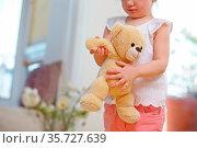 Kind trägt Kuscheltier mit beiden Händen zu Hause. Стоковое фото, фотограф Zoonar.com/Robert Kneschke / age Fotostock / Фотобанк Лори