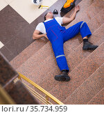 Dead contractor worker felling off the stairs. Стоковое фото, фотограф Elnur / Фотобанк Лори