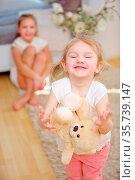 Zwei Kinder spielen mit einem Teddy als Kuscheltier zu Hause. Стоковое фото, фотограф Zoonar.com/Robert Kneschke / age Fotostock / Фотобанк Лори