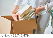 Frau packt Bücher in einen Umzugskarton für den Umzug in das neue Haus. Стоковое фото, фотограф Zoonar.com/Robert Kneschke / age Fotostock / Фотобанк Лори