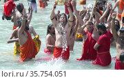 Kumbh Mela Haridwar India. Slowmotion shot of Sadhus or Saints of Akharas taking bath in Holy Water of River Ganges. Worship with religious ornament.. Appleprores 422 Cinetone. Редакционное видео, видеограф Devendra Rawat / Фотобанк Лори