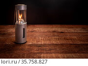 Collapsible camping candle lantern burning in darkness on a rustic... Стоковое фото, фотограф Zoonar.com/Marek Uliasz / easy Fotostock / Фотобанк Лори
