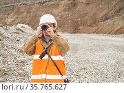 Mining or road engineer using a telescope against the background of a mine. Стоковое фото, фотограф Евгений Харитонов / Фотобанк Лори