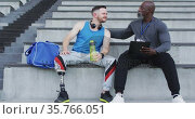 Diverse male coach and disabled athlete with prosthetic leg talking during training session. Стоковое видео, агентство Wavebreak Media / Фотобанк Лори