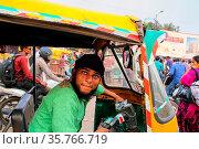 Young man driving tuk-tuk at Kinari Bazaar in Agra, Uttar Pradesh... Стоковое фото, фотограф Zoonar.com/Don Mammoser / age Fotostock / Фотобанк Лори