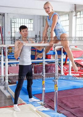 Man coaching woman doing exercises on bars