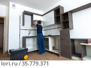 Рабочий собирает модульную мебель в малогабаритной квартире (2018 год). Редакционное фото, фотограф Виктор Карасев / Фотобанк Лори