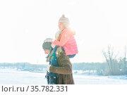 Vater trägt seine Tochter huckepack im Winter im Schnee. Стоковое фото, фотограф Zoonar.com/Robert Kneschke / age Fotostock / Фотобанк Лори