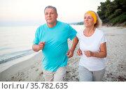 Senior man and woman having a run along the shore. Scene with sea... Стоковое фото, фотограф Zoonar.com/Danil Roudenko / age Fotostock / Фотобанк Лори
