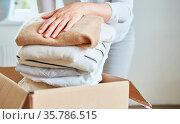 Frau packt Kleidung für eine Kleiderspende in einen Karton oder räumt... Стоковое фото, фотограф Zoonar.com/Robert Kneschke / age Fotostock / Фотобанк Лори