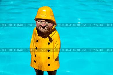 Fisherman wooden figure with yellow rain coat and smoke pipe on swimming...