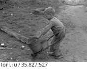 Child of white migrant worker playing with automobile tools near Harlingen, Texas By Russell Lee, 1903-1986, photographer Date 19390101. Редакционное фото, агентство World History Archive / Фотобанк Лори