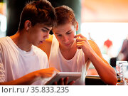 Two male teenagers surfing the internet on tablet computer while ... Стоковое фото, фотограф Zoonar.com/Danil Roudenko / age Fotostock / Фотобанк Лори