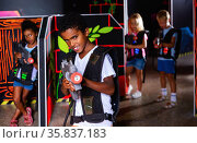 Portrait of mulatto tweenager boy with laser gun having fun on dark lasertag arena. Стоковое фото, фотограф Яков Филимонов / Фотобанк Лори