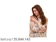 Young beautiful woman looks thoughtfully to the side, clasping herself with her arms, isolated on white background. Стоковое фото, фотограф Евгений Харитонов / Фотобанк Лори