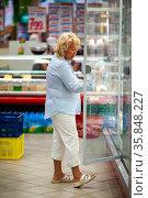 Senior woman choosing dairy in the store. She taking the bottle from... Стоковое фото, фотограф Zoonar.com/Danil Roudenko / age Fotostock / Фотобанк Лори