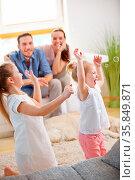 Kinder fangen Seifenblasen mit Familie zu Hause. Стоковое фото, фотограф Zoonar.com/Robert Kneschke / age Fotostock / Фотобанк Лори