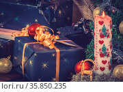 Christmas gifts with a Xmas candle and shiny baubles. Стоковое фото, фотограф Zoonar.com/Kasper Nymann / age Fotostock / Фотобанк Лори