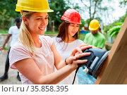 Zwei Frauen in der Schreiner Ausbildung arbeiten mit einer Schleifmaschine. Стоковое фото, фотограф Zoonar.com/Robert Kneschke / age Fotostock / Фотобанк Лори