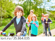 Kinder im internationalen Kindergarten machen einen Ausflug mit Roller... Стоковое фото, фотограф Zoonar.com/Robert Kneschke / age Fotostock / Фотобанк Лори