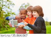 Drei Kinder machen Grimassen für ein Selfie Foto mit dem Smartphone... Стоковое фото, фотограф Zoonar.com/Robert Kneschke / age Fotostock / Фотобанк Лори