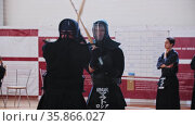 RUSSIA, KAZAN 24-04-2021: Kendo tournament indoors - two fighters in black costumes having a duel on bamboo sticks. Редакционное видео, видеограф Константин Шишкин / Фотобанк Лори
