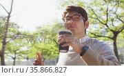 Asian man drinking coffee and having a snack while walking outdoors. Стоковое видео, агентство Wavebreak Media / Фотобанк Лори
