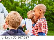 Kinder machen zusammen eine Geländespiel oder eine Schatzsuche im... Стоковое фото, фотограф Zoonar.com/Robert Kneschke / age Fotostock / Фотобанк Лори