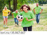 Frau und Kollegen machen zusammen ein Wettrennen mit Fußball beim... Стоковое фото, фотограф Zoonar.com/Robert Kneschke / age Fotostock / Фотобанк Лори