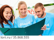 Team Freiwilliger im Ehrenamt studiert Blutspender Liste bei der ... Стоковое фото, фотограф Zoonar.com/Robert Kneschke / age Fotostock / Фотобанк Лори