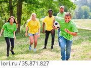 Junge Leute machen ein Wettrennen mit Fußball im Teambuilding Workshop. Стоковое фото, фотограф Zoonar.com/Robert Kneschke / age Fotostock / Фотобанк Лори