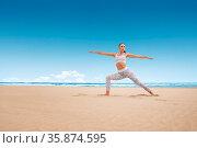 Young woman practice yoga posture warrior pose virabhadrasana at sunny... Стоковое фото, фотограф Zoonar.com/Svetlana Radayeva / easy Fotostock / Фотобанк Лори