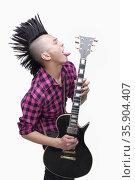 Young man with punk Mohawk playing guitar. Стоковое фото, агентство Ingram Publishing / Фотобанк Лори