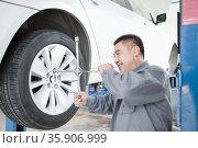 Mechanic Adjusting Tire. Стоковое фото, агентство Ingram Publishing / Фотобанк Лори
