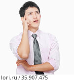 Young man with hand on face thinking. Стоковое фото, агентство Ingram Publishing / Фотобанк Лори