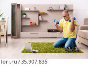 Aged man doing sport exercises at home. Стоковое фото, фотограф Elnur / Фотобанк Лори